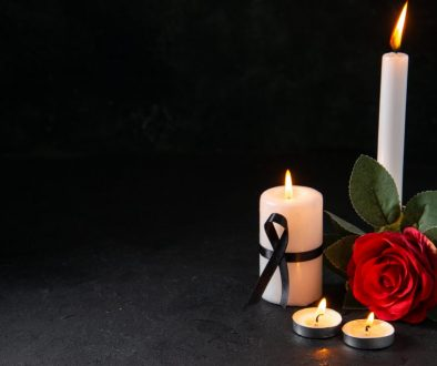 front-view-burning-candle-with-red-flower-dark-surface